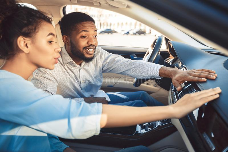 Afro couple at car showroom touching dash of new auto royalty free stock photo