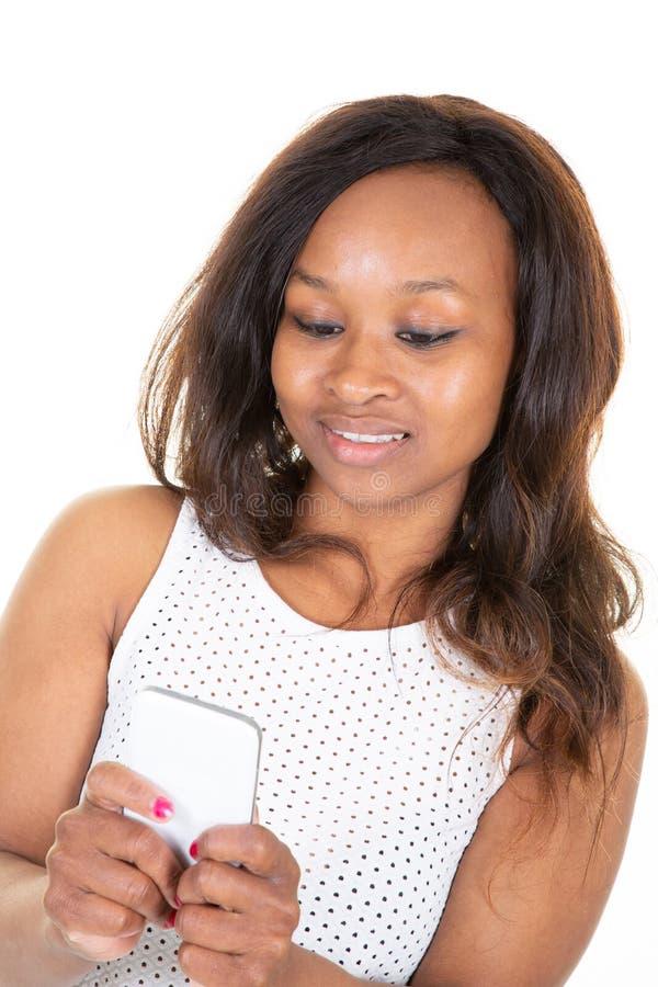 Afro de comunicação da mulher usando o telefone celular que olha abaixo do isolado sobre o fundo branco foto de stock