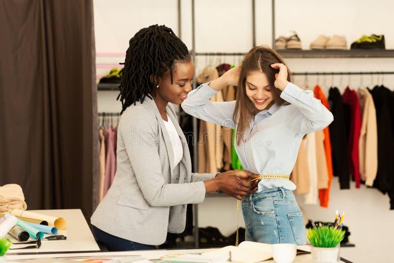 Afro Dressmaker Girl Measuring Client In Lavori Con Atelier fotografia stock