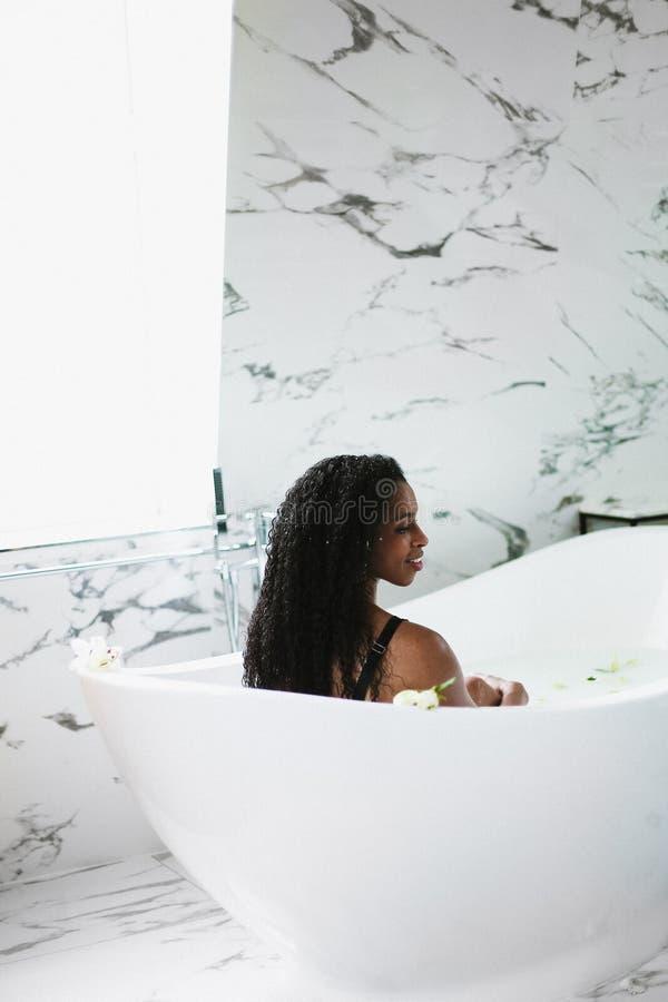 Afro dziewczyny amerykański brać kąpielowy i relaksować w łazience z marmur płytką fotografia stock