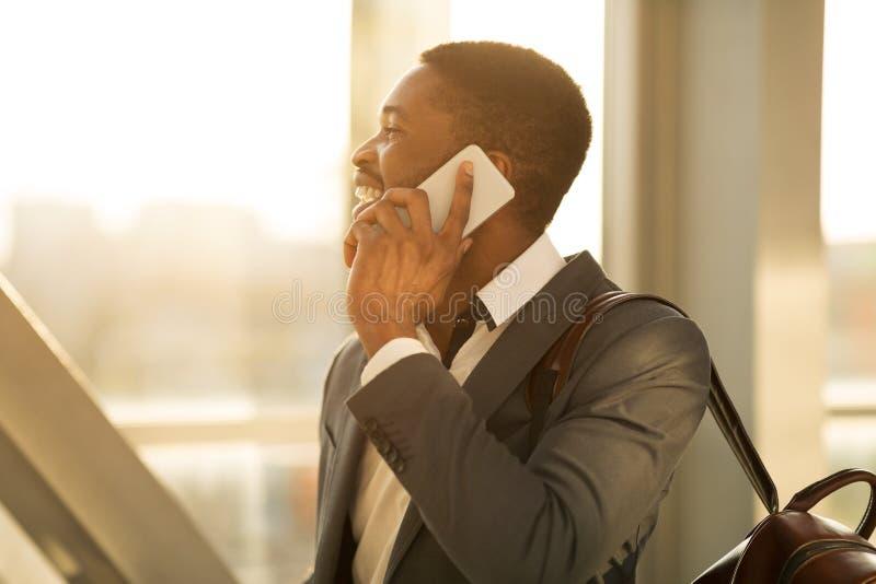 Afro finansista Opowiada na telefonie w Lotniskowy Śmiertelnie obrazy royalty free