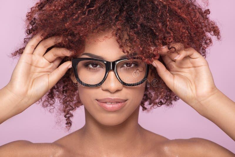 Afro- flicka i glasögon som ler royaltyfri fotografi