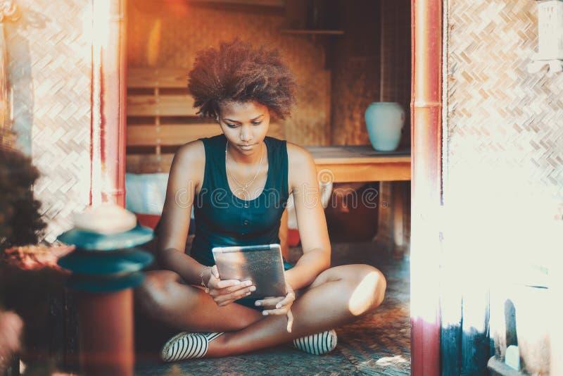 Afro- flicka på sommarverandan med minnestavlaPC royaltyfria bilder