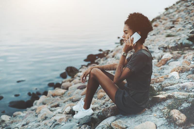 Afro- flicka som talar på telefonen nära floden arkivbilder