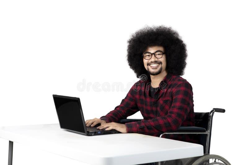 Afro gehandicapte student die laptop met behulp van stock fotografie