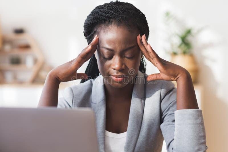 Afro Geschäftsfrau, die den Tempel massiert und versucht, sich auf die Arbeit zu konzentrieren stockfotos