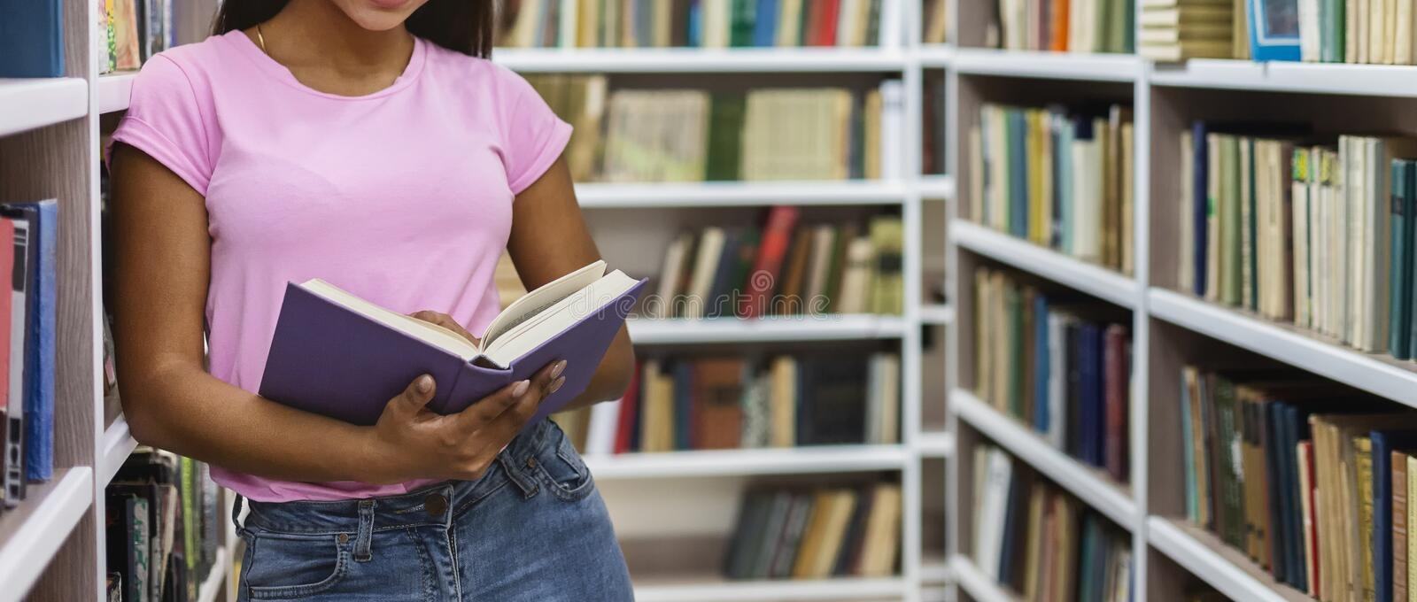 Afro girl holding open book, leaning on bookshelf. Black girl holding open book, leaning on bookshelf at library, copy space stock photo