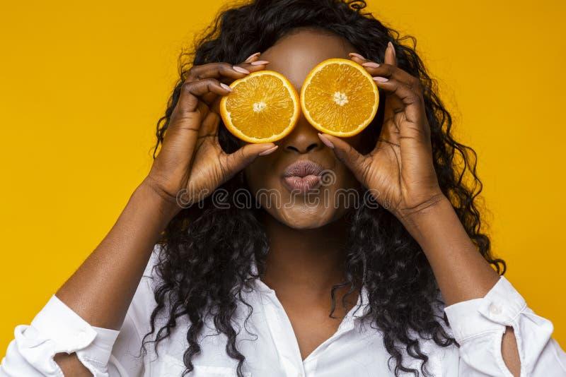 Afro girl holding two halves of orange next to eyes stock photo