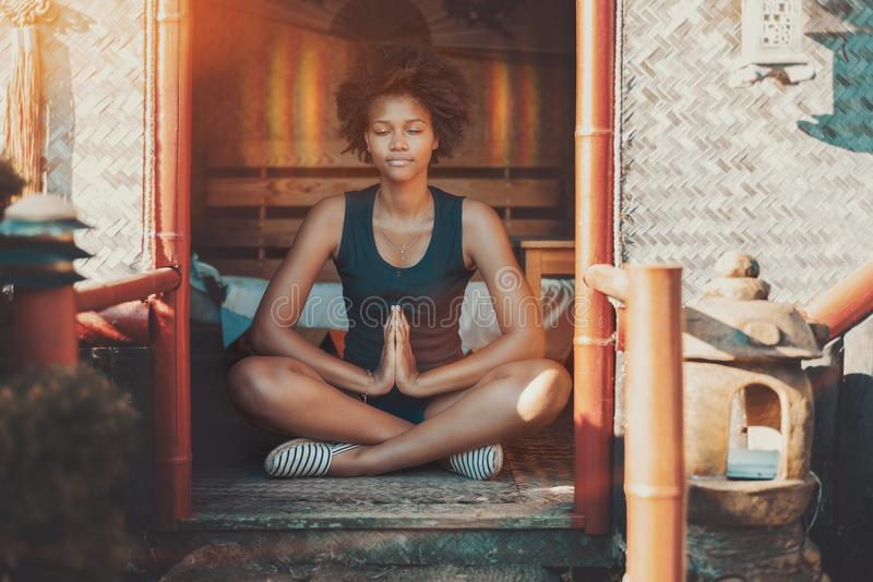 Afro girl meditating with glow over her head stock photography