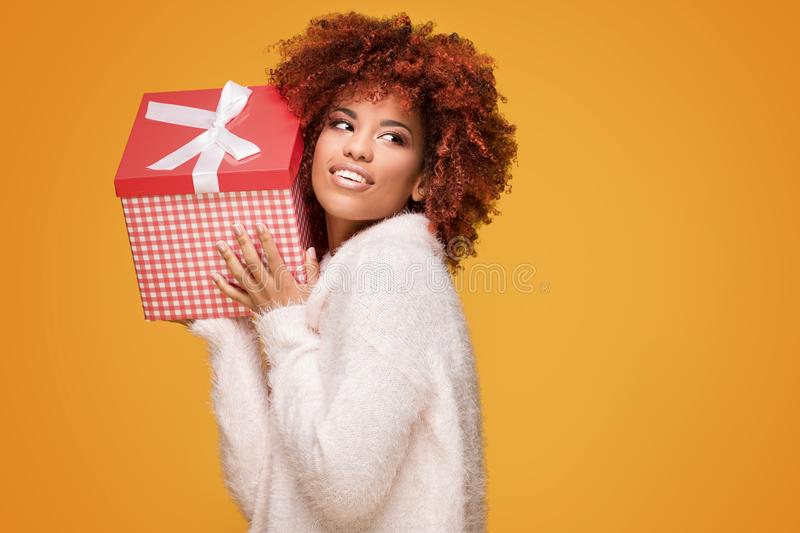 Afro girl posing with gift box, smiling. stock photos