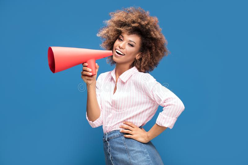 Afro girl screaming by megaphone. Smiling beautiful young African American woman with curly afro hair screaming by megaphone stock photography