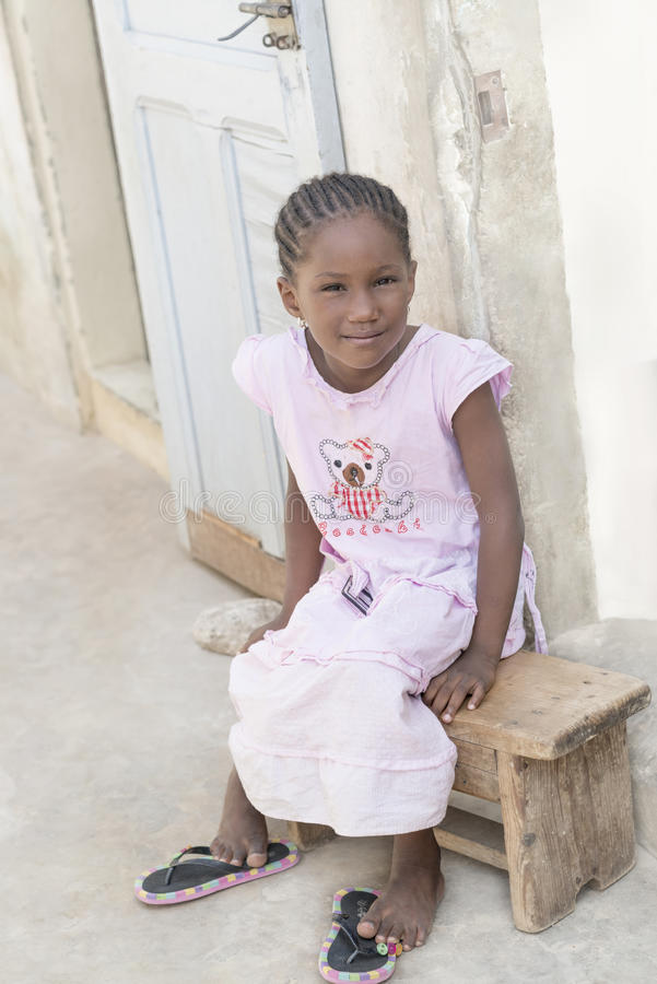 Afro girl sitting on a bench, 6 years old stock photos