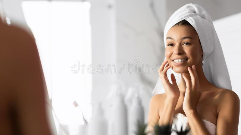Afro Girl Touching Face Looking In Mirror In Bathroom. Panorama royalty free stock image