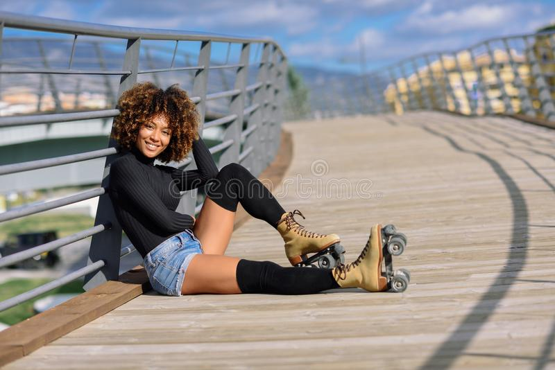 Afro hairstyle woman on roller skates sitting on urban bridge. Black woman, afro hairstyle, on roller skates sitting outdoors on urban bridge. Smiling young stock photo