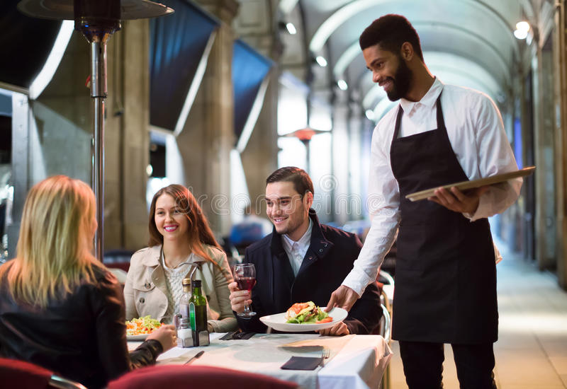 Afro kelner bierze stołowego rozkaz i ono uśmiecha się obrazy royalty free