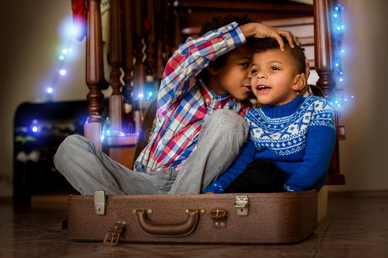 Afro kids whispering and smiling. royalty free stock photography