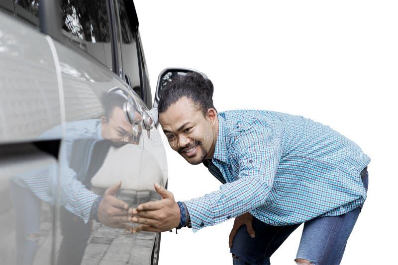 Afro mężczyzna podziwia jej wymarzonego samochód w studiu obraz stock