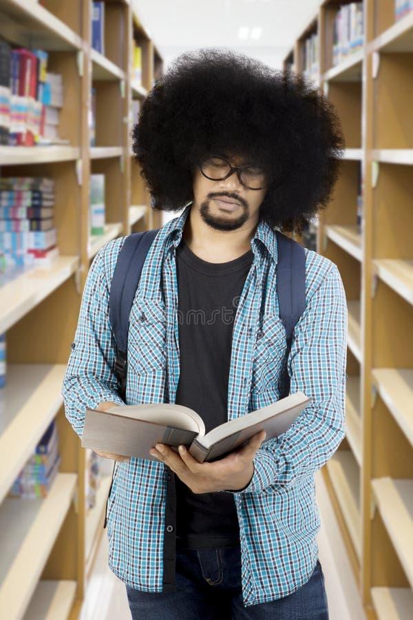 Afro męski uczeń czyta książkę przy biblioteką zdjęcie stock