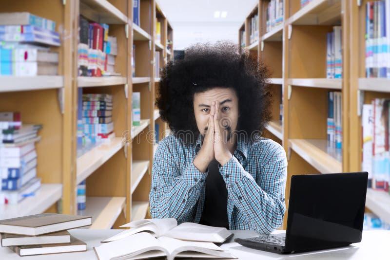 Afro męskiego ucznia spojrzenia męczący przy biblioteką obraz stock