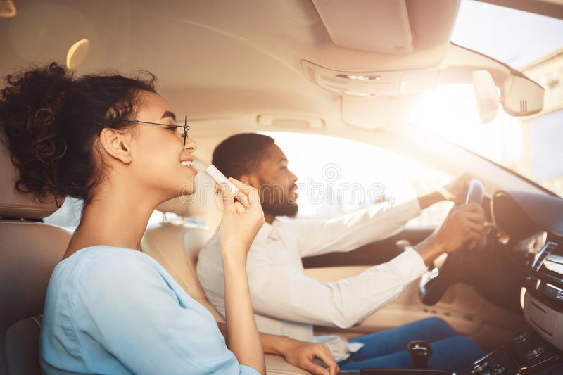 Afro man driving car, his girlfriend applying lipstick stock photo
