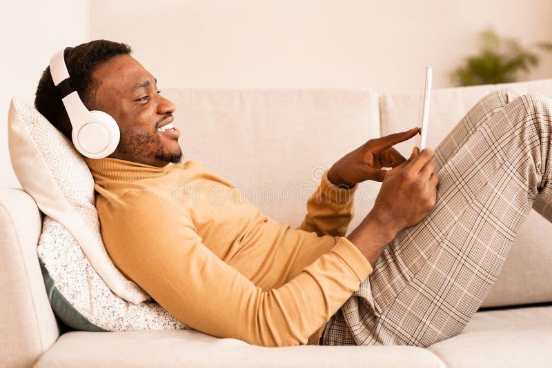 Afro Man In Earphones Usando Tablet Deitado Em Sofá No Interior imagens de stock royalty free