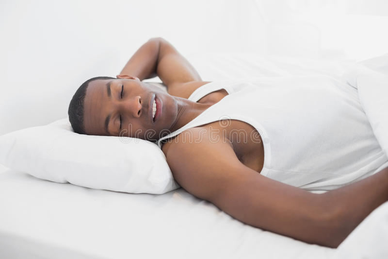 Afro man sleeping in bed. Young Afro man sleeping in bed at home royalty free stock photos