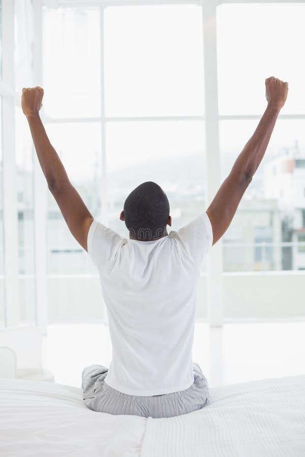 Afro- man som vaknar upp i säng och sträcker hans armar arkivbild