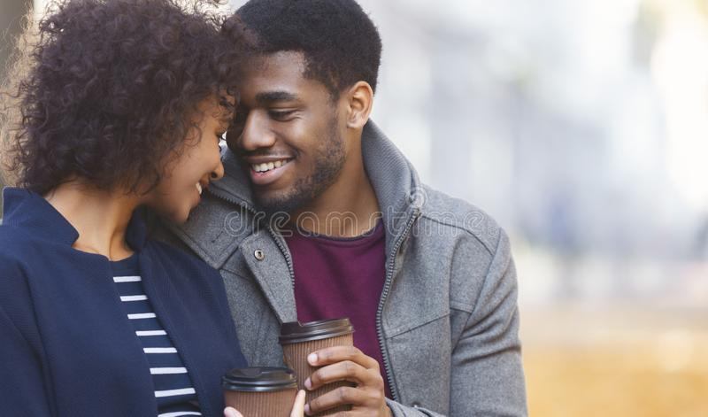 Afro man and woman warming up with coffee in park royalty free stock photo