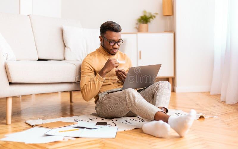 Afro Man Working On Laptop Having Coffee Sitting On Floor stock photos