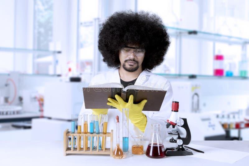 Afro naukowiec czyta książkę w laboratorium obraz royalty free