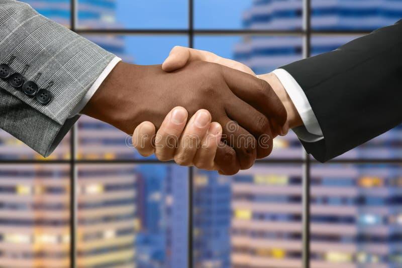 Afro- och caucasian affärsmäns handskakning arkivfoton