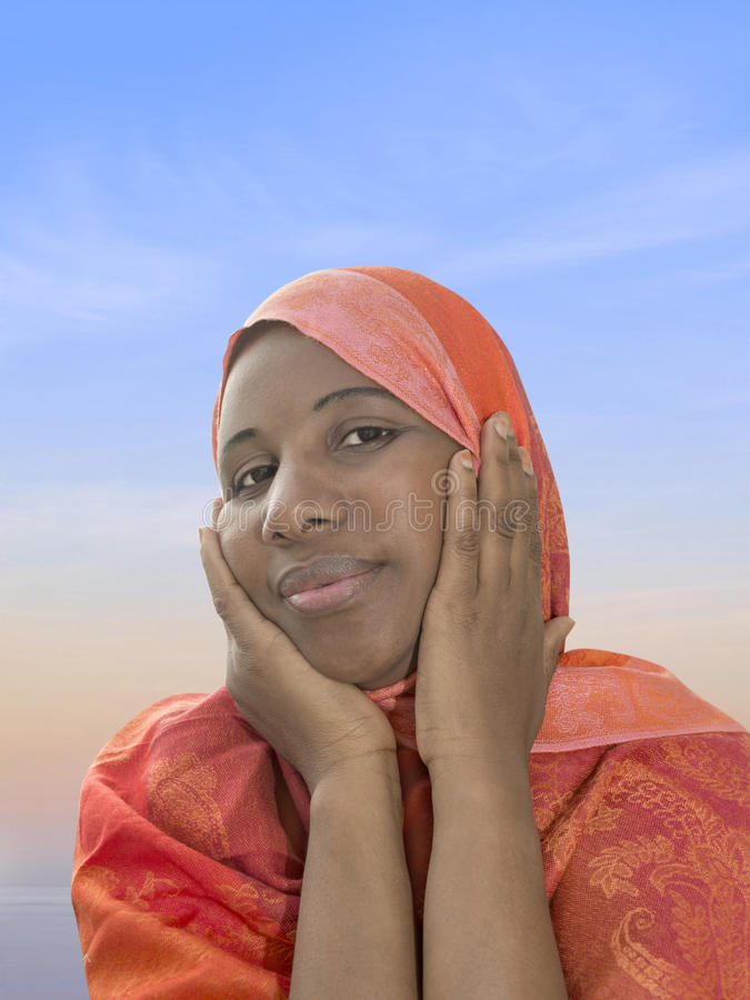 Afro- skönhet som bär en orange sjalett i morgonljuset royaltyfri fotografi
