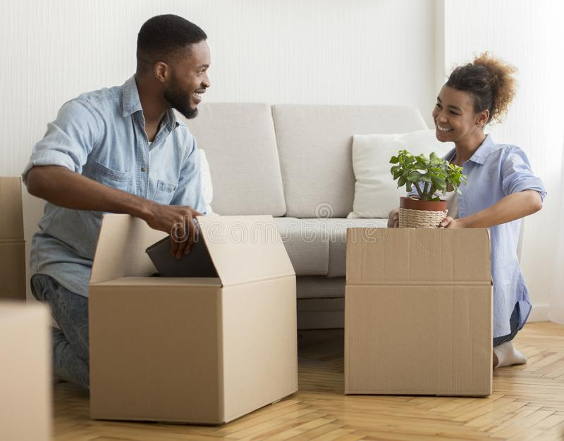 Afro Spouses Packing Boxes Together Sitting On Floor At Home stock image