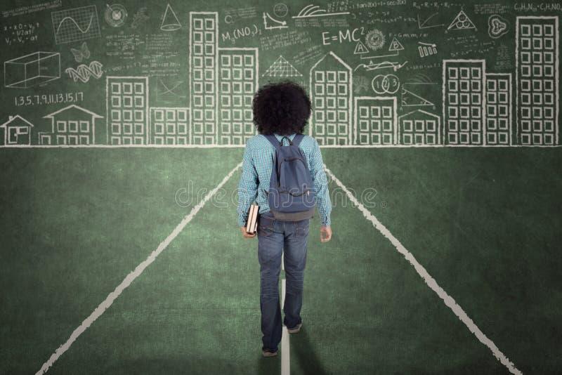 Afro student collegu odprowadzenie na chalkboard obrazy stock