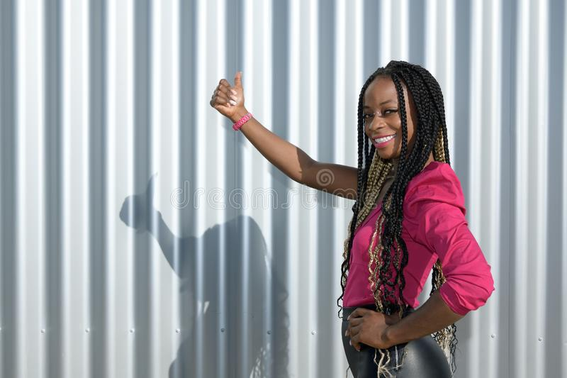 Afro-style black girl with long black and blondes braids smiles and waved while looks at the camera with a metallic fence in the royalty free stock image