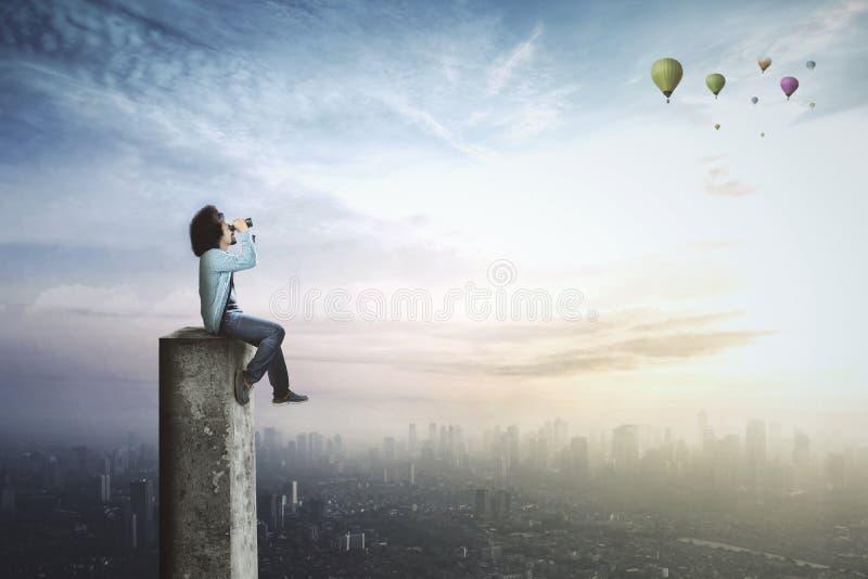 Afro ucznia spojrzenia przy lotniczymi balonami z lornetkami zdjęcia stock