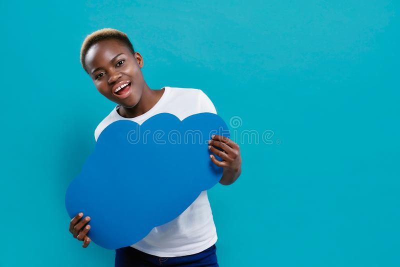 Afro woman holding blue paper speech bubble in form of cloud stock photos