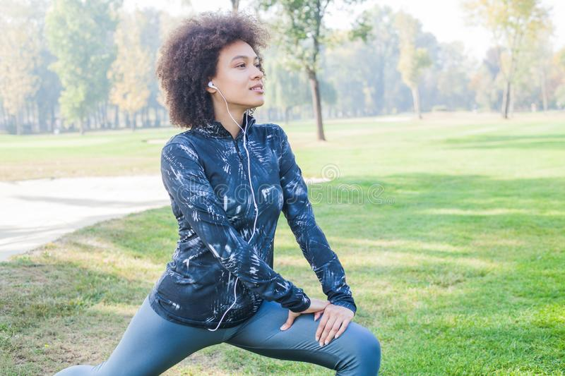Afro Woman Listening Music While Exercising At Park stock photos