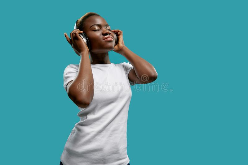 Afro woman listening music with headphones with closed eyes. royalty free stock photography