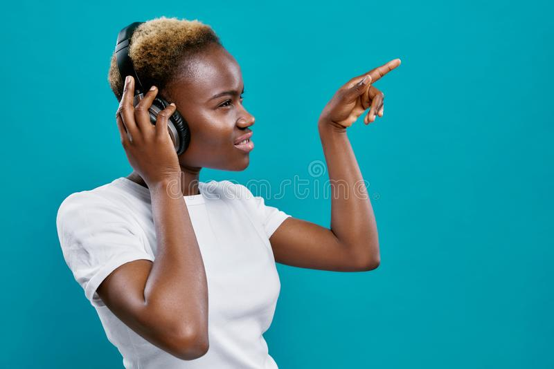 Afro woman with short hair listening music with headphones. stock image