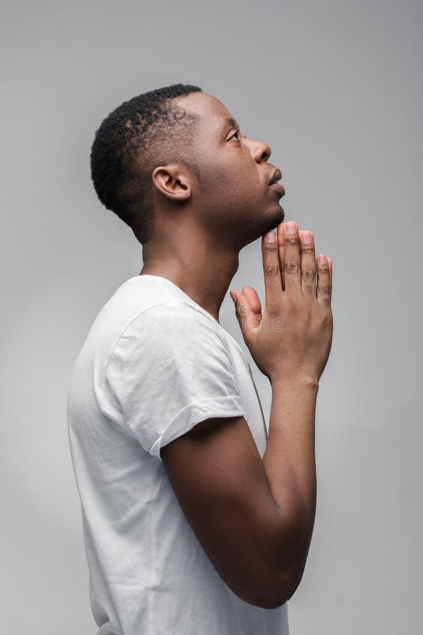 Afroamerican парень моля и спрашивая богу Профиль стоковые фотографии rf