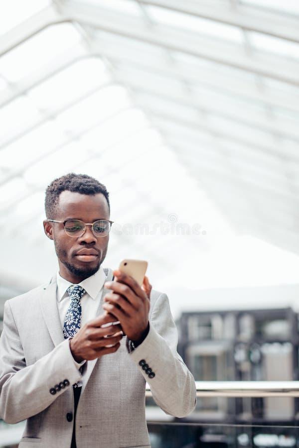 Afroamerican biznesmen texting na telefonie w centrum handlowym lub sala nowożytny biuro obrazy stock