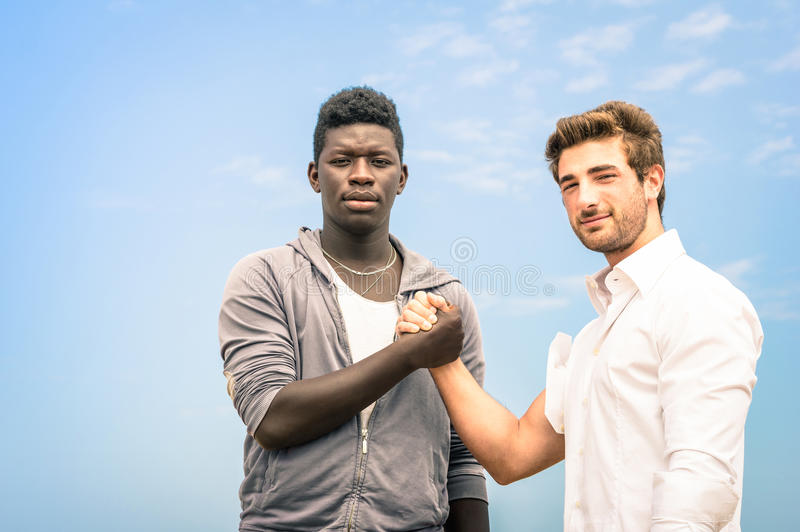 Afroamerican and caucasian men shaking hands. In a modern handshake to show each other friendship and respect - Arm wrestling against racism royalty free stock photography