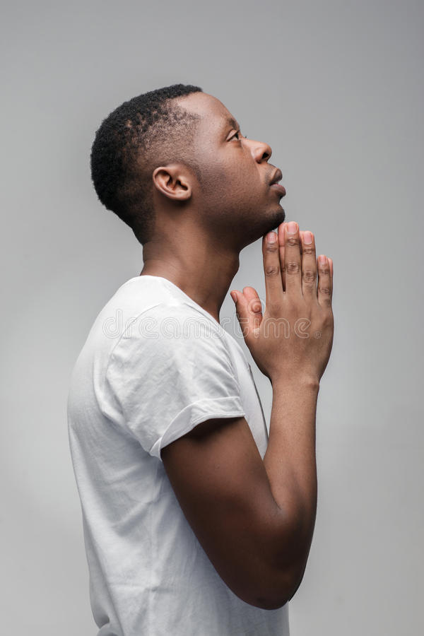 Afroamerican guy praying and asking God. Profile. royalty free stock photos