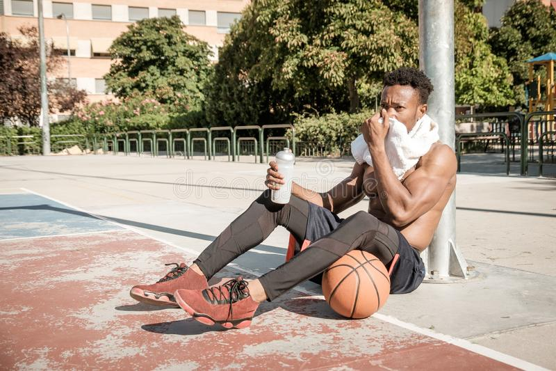 Afroamerican młody człowiek bawić się uliczną koszykówkę w parku zdjęcie stock