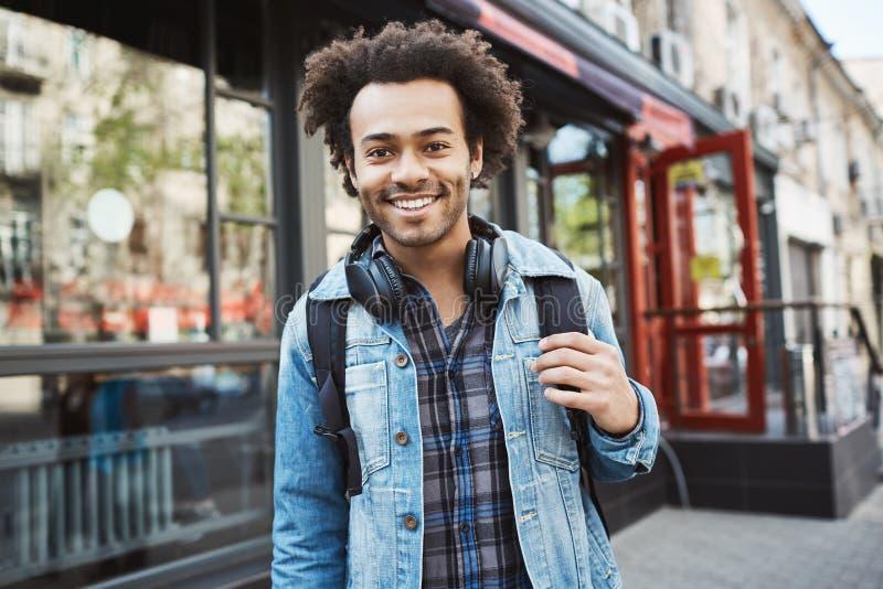 Afroamericano alla moda bello con il cappotto e le cuffie d'uso del denim dell'acconciatura di afro che cammina la città Studente fotografia stock libera da diritti
