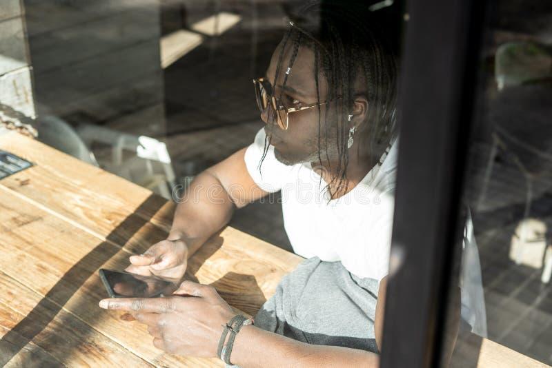 Afroamericano bello che esamina un telefono cellulare in una caffetteria immagine stock