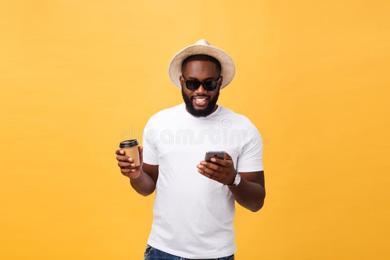 Afroamericano hermoso con el teléfono móvil y llevarse la taza de café Aislado sobre fondo del oro amarillo imagenes de archivo