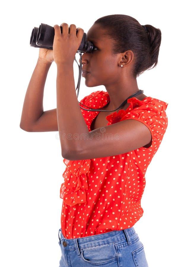 Afroamericano que usa los prismáticos aislados sobre el fondo blanco foto de archivo