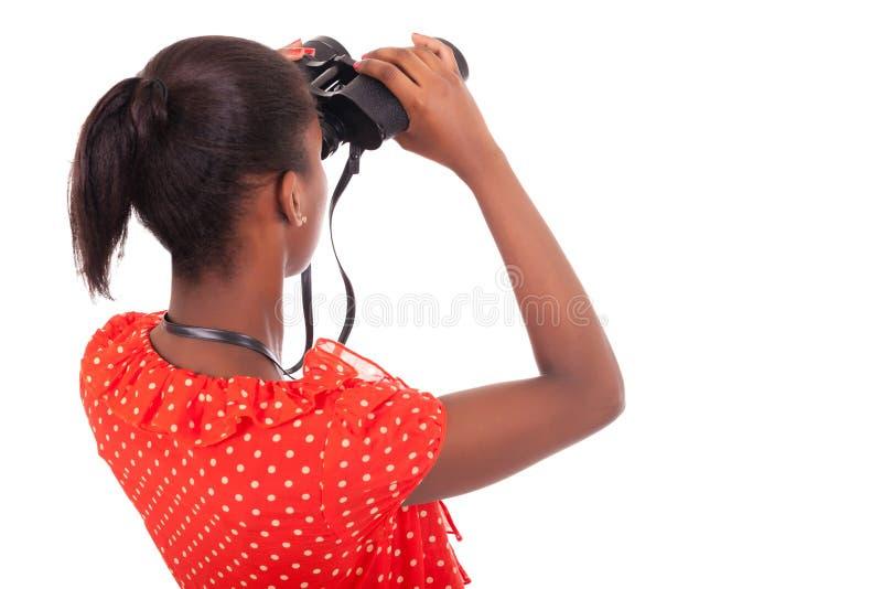 Afroamericano que usa los prismáticos aislados sobre el fondo blanco imagen de archivo